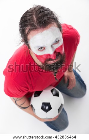 male polish soccer fan looks unhappy, holding a ball in his hands, topview