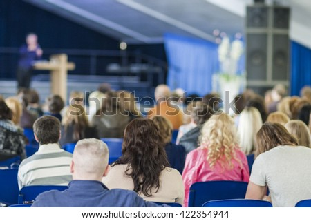 Male Professional Lecturer Speaking In front of the People. Horizontal Image Composition. - stock photo