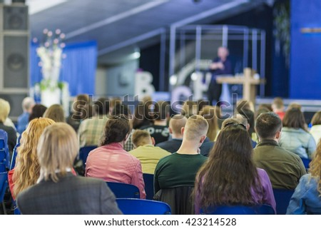 Male Professional Lecturer Speaking In front of the People. Horizontal Image Composition - stock photo