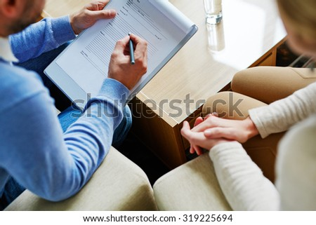Male psychiatrist making notes with his patient near by - stock photo