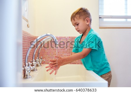 Male Pupil At Montessori School Washing Hands In Washroom