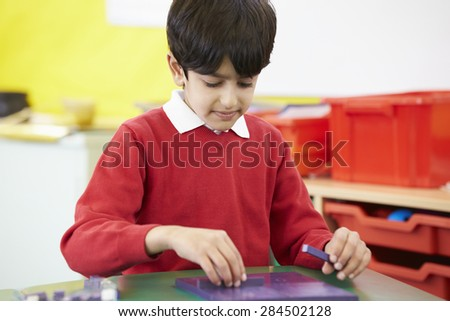Male Pupil Practising Maths At Desk