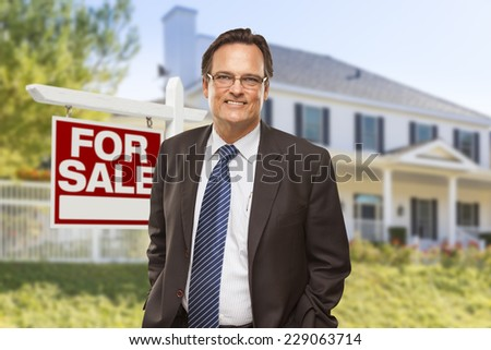 Male Real Estate Agent in Front of Home For Sale Sign and House. - stock photo