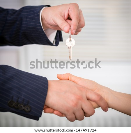 Male realtor giving a key of a new family house to female client in the office.  - stock photo