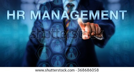 Male recruiter is pressing HR MANAGEMENT on a touch screen interface. Male and female employee icons contained in virtual hexagons do shape a planning matrix. Business and technology concept. - stock photo
