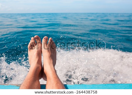 Male relaxing his feet over the edge of boat. Travel concept. - stock photo