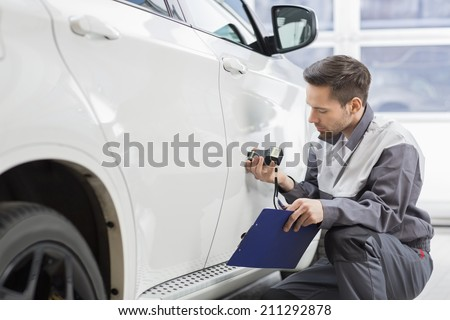 Male repair worker examining car paint with equipment in repair shop - stock photo