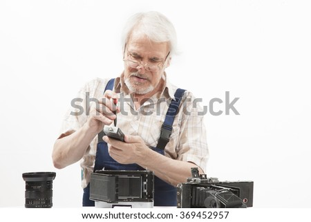 Male repairing an old camera at his workplace on white background