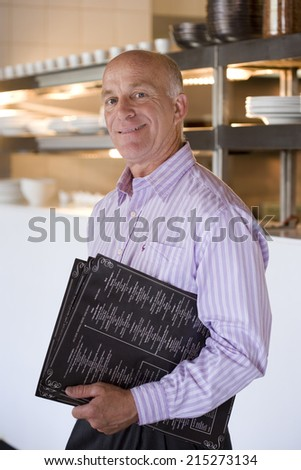 Male restaurant manager standing in commercial kitchen, carrying menus, smiling, side view, portrait - stock photo