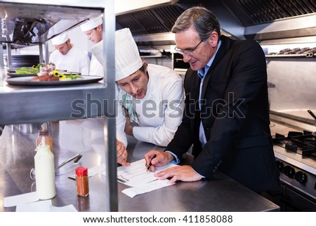 Male restaurant manager writing on clipboard while interacting to head chef in commercial kitchen - stock photo