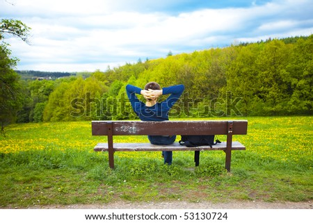 male resting on the bench on the field of dandelions - stock photo