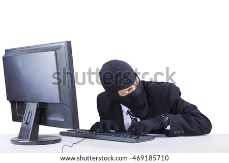 Male robber wearing mask and steal information on the computer while looking at around him
