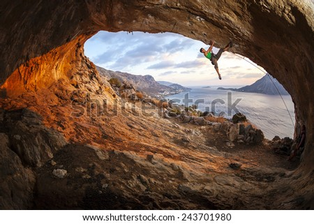 Male rock climber climbing along a roof in a cave at sunset  - stock photo