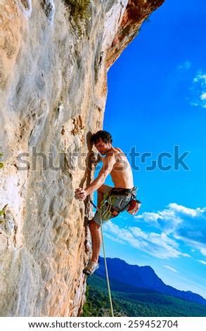 male rock climber climbs on a rocky wall