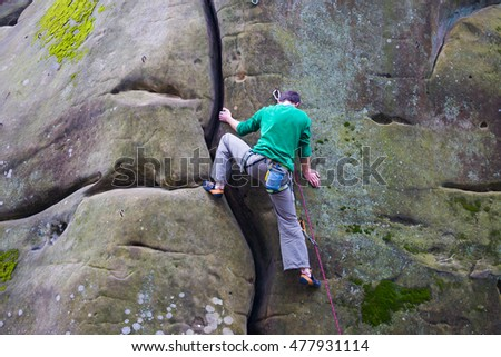 Male rock climber climbs up the mountain.
