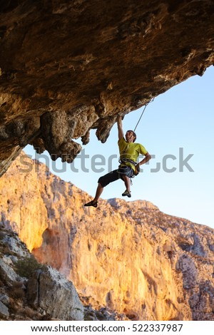 Male rock climber hanging with one hand on a cliff while putting chalk on another