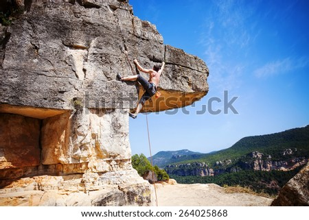 Male rock climber on a cliff - stock photo
