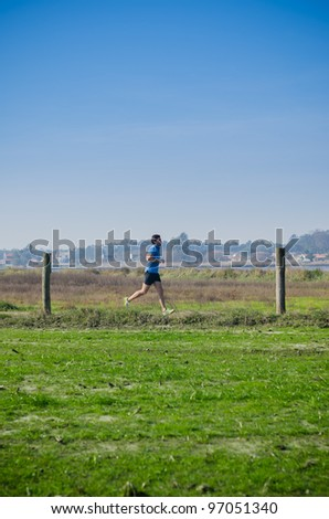 Male runner at sprinting speed training for marathon outdoors on country landscape. - stock photo