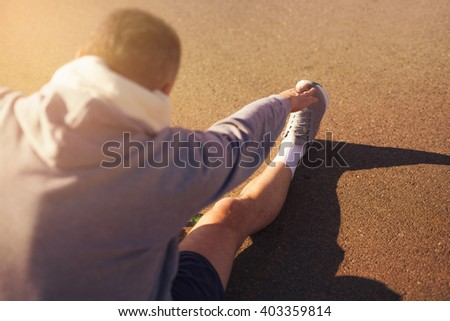 Male runner doing stretching exercise. Selective focus - stock photo