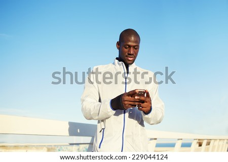 Male runner in white windbreaker resting after run while typing something on his mobile smart phone, black man holding smart phone resting after fitness training outdoors, people using technology  - stock photo