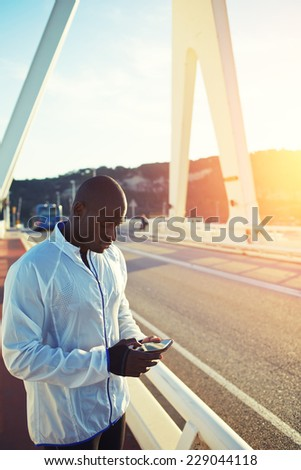 Male runner in white windbreaker typing something on his mobile smart phone standing at sunset on beautiful road, black man holding smart phone resting typing something, fit man wit mobile smart phone - stock photo
