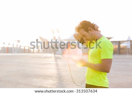 Male runner is uses a mobile phone to switch music on the play-list with copy space for text advertising, young sportsman stopped on the road after an active run while listening to music in headphones - stock photo