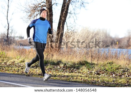 Male runner man running in autumn on cold day wearing long tights and long sporty jogging outfit. Fit male fitness athlete model training outdoor in fall. Full body length of jogger. - stock photo