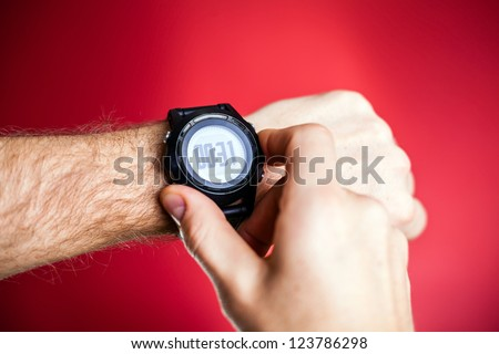 Male runner ready to run with sport watch smartwatch. Taking pulse trace or checking gps position wristwatch, using wearable heart monitor. Man and fitness, exercising concept.