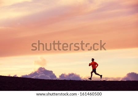 Male runner silhouette, Man running into sunset, colorful sunset sky  - stock photo