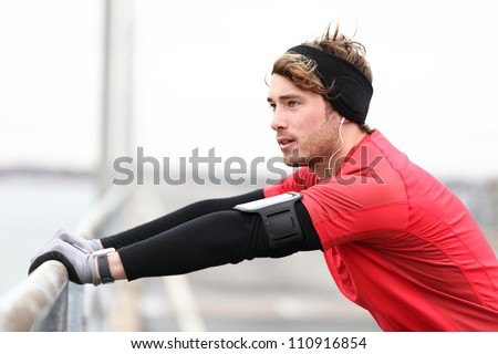 Male runner stretching after running in cold fall weather wearing warm sporty running clothing. Handsome male fitness sport model outdoors. - stock photo
