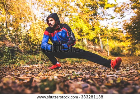 Male runner stretching before workout. - stock photo
