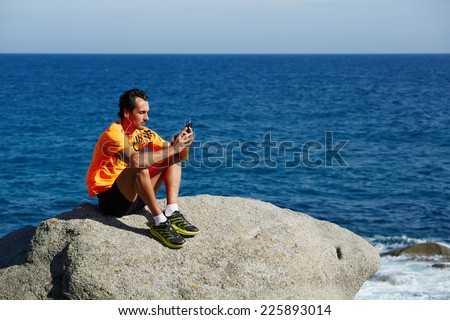 Male runner using mobile smart phone resting after workout, sportsman in fluorescent t-shirt rest and relax after the training outdoors, male jogger seated on the beach enjoying music, sport lifestyle - stock photo