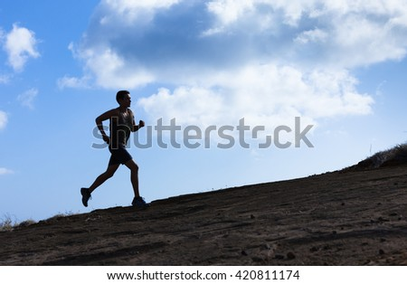 Male running up a hill.