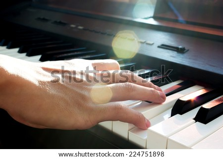 Male's hand playing piano  with light trough and flare light. - stock photo