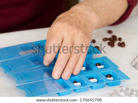 Male's hand sorting drugs in blue pills container - stock photo