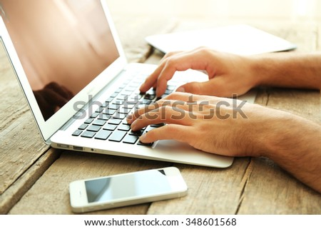 Male's hands taping on laptop on wooden table in office - stock photo