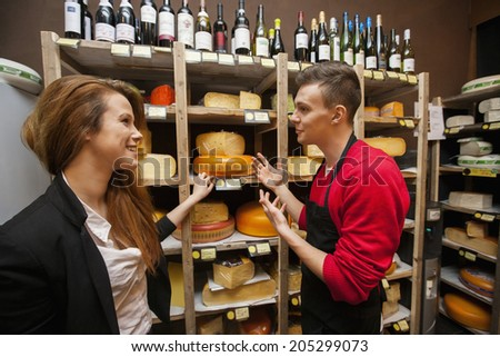 Male salesperson showing cheese to female customer in store