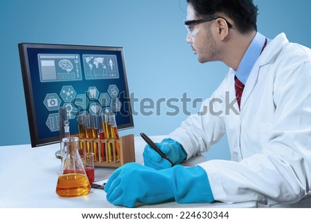 Male scientist looking at monitor and write research report on clipboard - stock photo