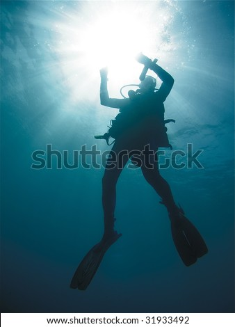 Male Scuba Diver Silhouette Ascending with Sun Rays and Blue Water in Background - stock photo