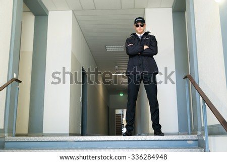 Male Security Guard Standing With Folded Arms At The Entrance - stock photo