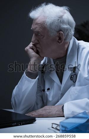Male senior doctor having problems at work - stock photo