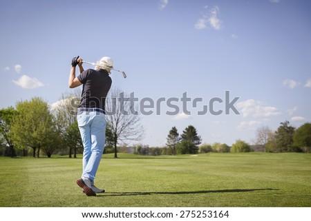 Male senior golf player hitting ball on fairway. - stock photo