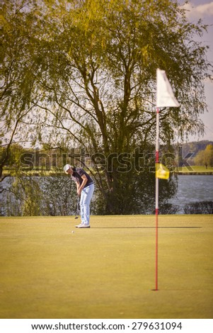 Male senior golf player putting on green with flag in foreground. - stock photo