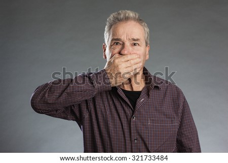 Male senior holding hands over mouth. Horizontal portrait on gray background with copy space - stock photo