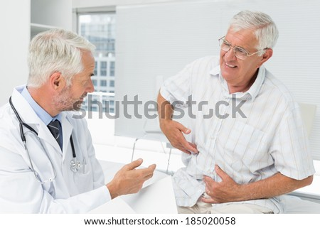 Male senior patient visiting a doctor at the medical office - stock photo