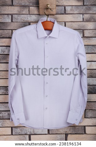 Male shirt on hanger on bricks wall background