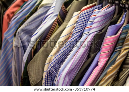 Male shirts hanging in a charity shop, close up  - stock photo