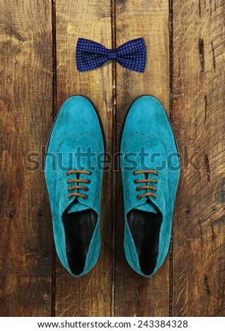 male shoes and bow-tie on a brown wooden background - stock photo