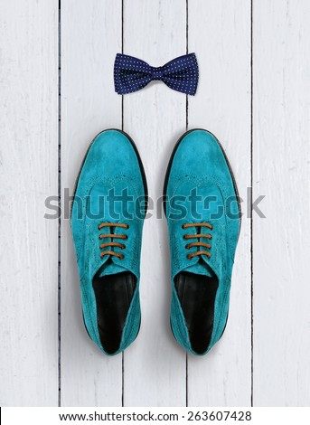 male shoes and bow-tie on a white wooden background - stock photo