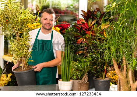 Male shop assistant potted plant flower working smiling - stock photo